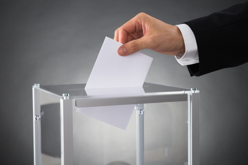 Businessperson Putting Ballot In Box